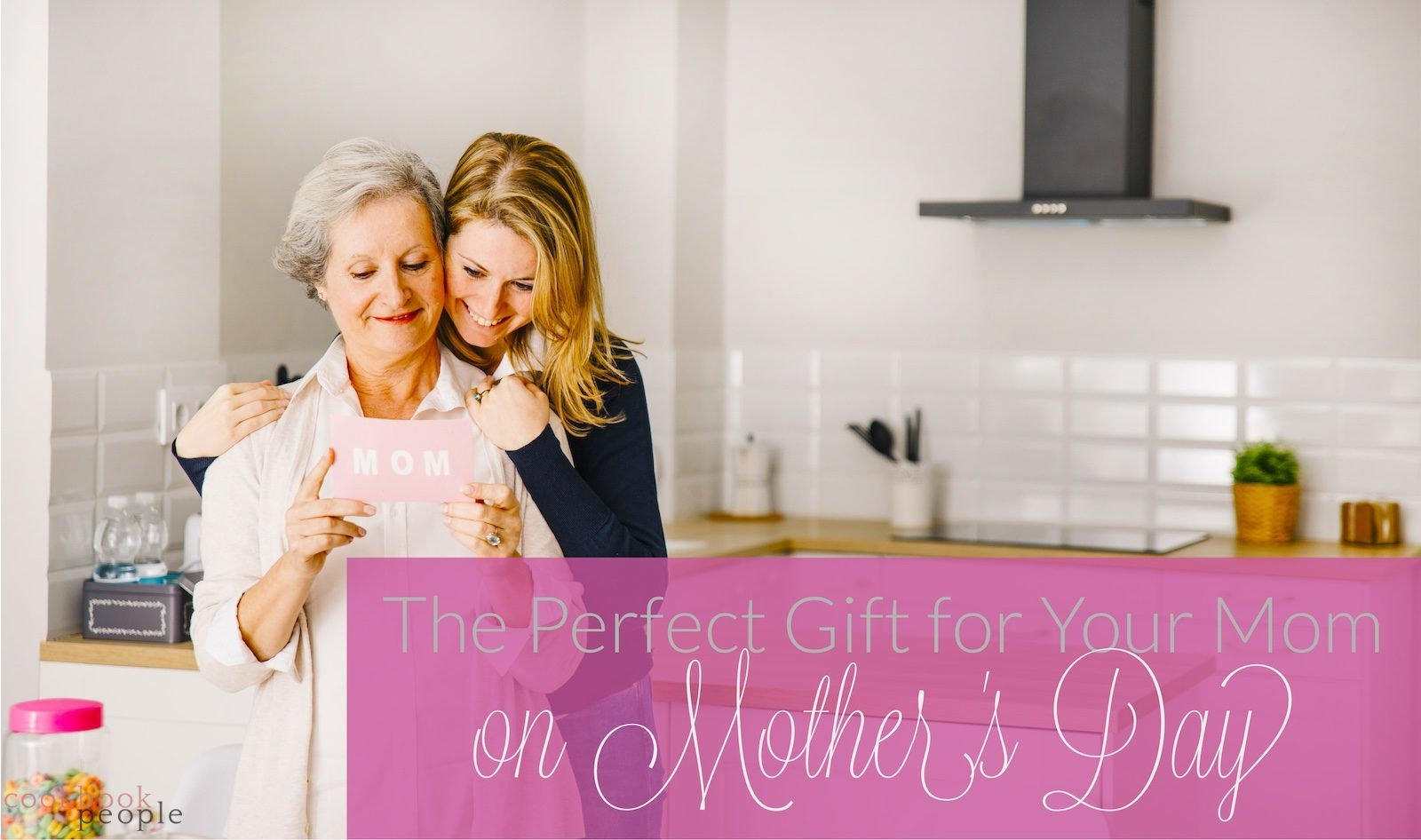 Daughter hugging Mom in kitchen overlaid with text: The Perfect Gift for Your Mom on Mother's Day